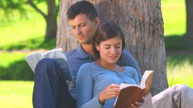 Young couple reading outdoors — Stock Video
