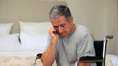 Hombre cansado, pensando en una silla de ruedas — Vídeo de stock