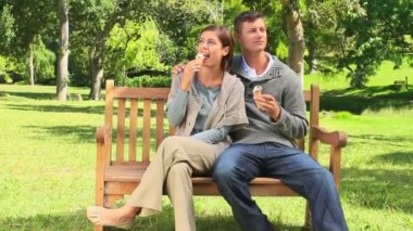 Young couple eating icecream on a bench — Stock Video