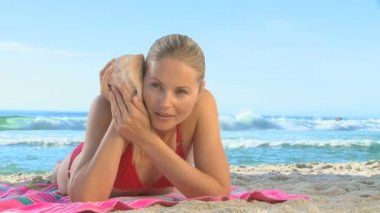Attractive blonde woman listening to a shell — Stock Video
