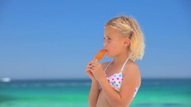 Little blonde girl eating a water ice — Stock Video