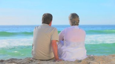 Mature couple relaxing sitting on a beach — Stock Video