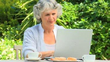 Frau arbeitet auf ihrem laptop im garten — Stockvideo