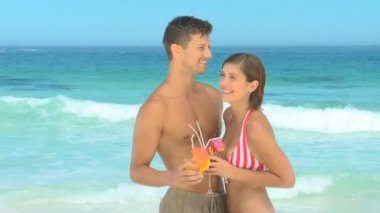 Beautiful couple having drinks on a beach — Stock Video