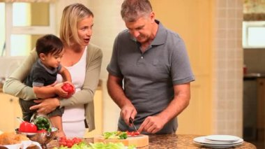 Father preparing vegetables while mother holds baby — Stockvideo