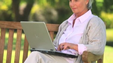 Mature woman chatting on her laptop — Stock Video