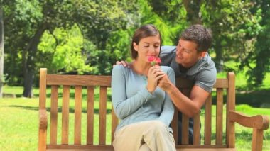 Young couple with a flower on a park bench — Stock Video