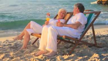 Mature couple talking sitting in deckchairs — Stock Video