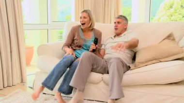 Couple on sofa ecstatic as they watch a programme on TV