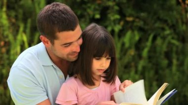 Father reading a book with his little girl — Stock Video