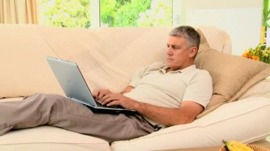 Man lying on coch working on his laptop — Stock Video