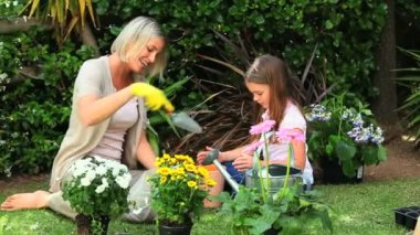 Little girl and mother potting flowers in garden — Stock Video