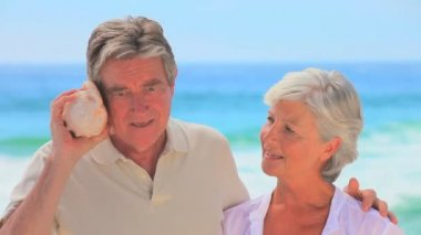 Mature couple listening to shell together — Stock Video