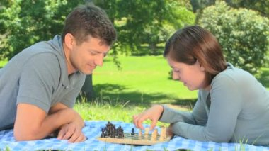 Young couple playing chess on the grass — Stock Video