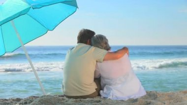 Elderly couple looking at the sea near a beach umbrella — Stock Video