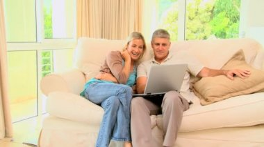 Couple on sofa enjoying a programme on their laptop — Vídeo Stock