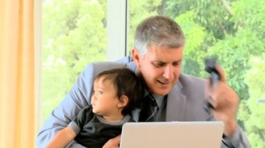 Businessman working at the desk with baby — Stock Video