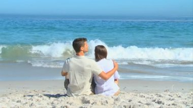 Cute couple hugging sitting in front of the sea — Stock Video