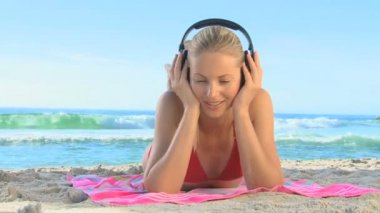 Blonde woman in a red swimsuit listening to music — Stock Video