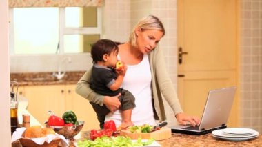 Mother coping with baby while cooking and using a laptop — Stock Video
