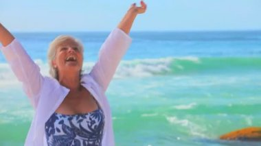 Mature woman dancing at the water's edge — Stock Video