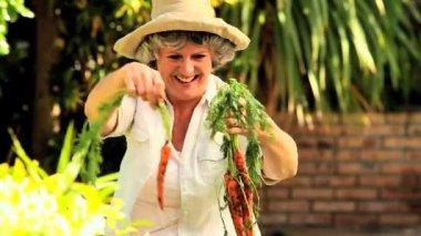 Mogen kvinna plocka upp rotfrukter i trädgården — Stockvideo