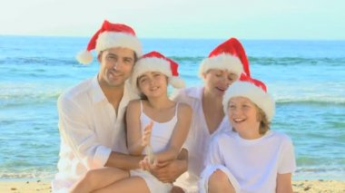 Happy family wearing Christmas hats on a beach — Stock Video
