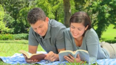 Smiling young couple reading outdoors — Stock Video