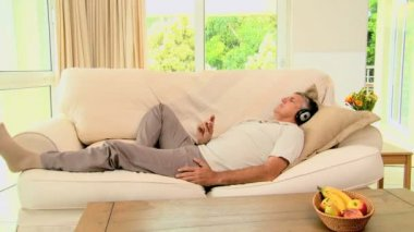 Man lying on sofa enjoying music with headphones — Stock Video