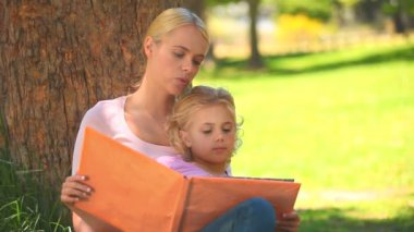Young mother and her daughter reading a book together — Stock Video