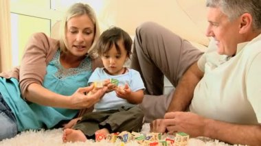 Doting parents and child playing with alphabet blocks — Stock Video