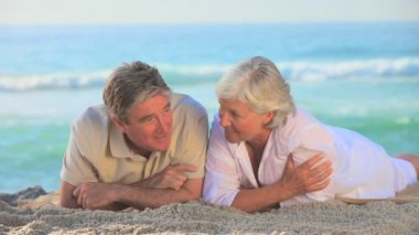Elderly couple lying on a beach — Stock Video