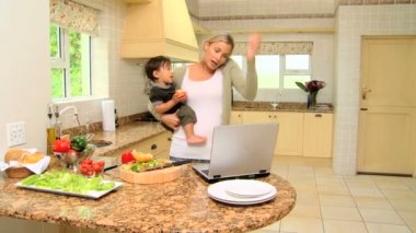 Busy woman holding baby while phoning and working on laptop — Stock Video