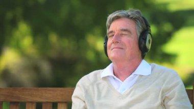 音楽を聞いている成熟した男性 — ストックビデオ
