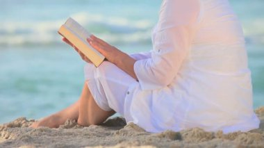 Mature woman sitting reading on a beach — Stock Video