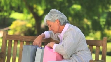 Mature woman on a park bench with her shopping — Stock Video