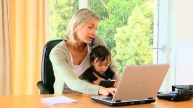 Jovem mãe tentando fazer trabalho de escritório com indisciplinados bebê no colo — Vídeo stock