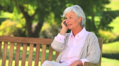 Mature woman phoning on a public bench — Stock Video