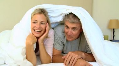 Young couple laughing and posing under the duvet — Stock Video