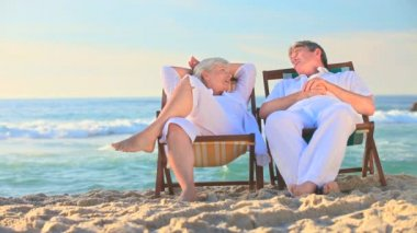 Elderly couple sitting in deckchairs on a beach — Stock Video