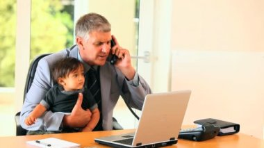 Man holding baby and answering phone at desk — Stock Video