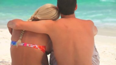 Cute couple hugging and relaxing in front of the sea — Stock Video