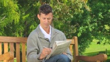 Young man doing crosswords outdoors — Stock Video