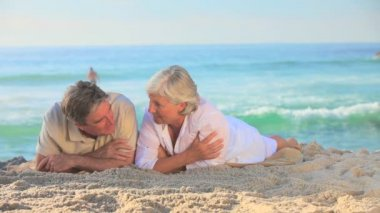 Elderly couple lying on the sand — Stock Video