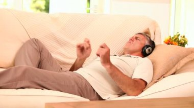Man lying on sofa listening to music with headphones — Stock Video