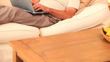 Man lying on sofa using laptop — Stock Video