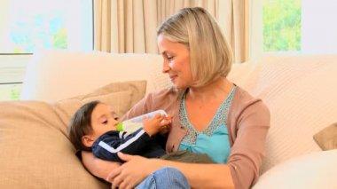 Young mother bottle-feeding baby on sofa — Stock Video