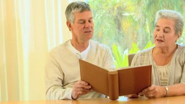 Mature couple reminiscing looking at an album — Stock Video