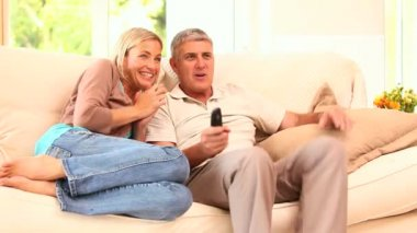 Young couple getting excited watching programme on TV — Stock Video