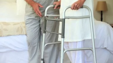Male nurse helping woman to walk with a zimmer frame — Stock Video